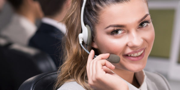 Young beautiful consultant talking through headset with her client